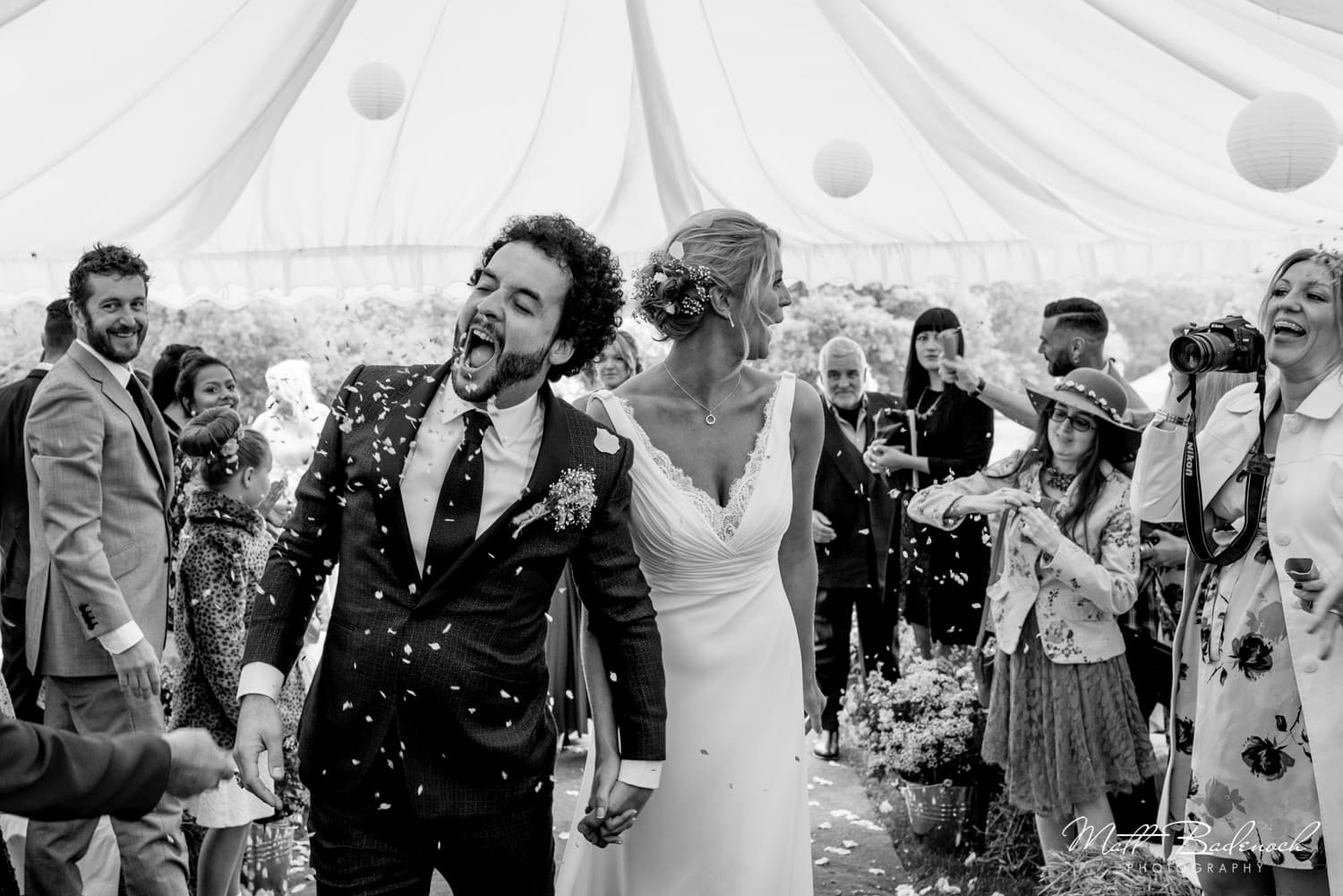 Groom eating confetti at his marquee wedding