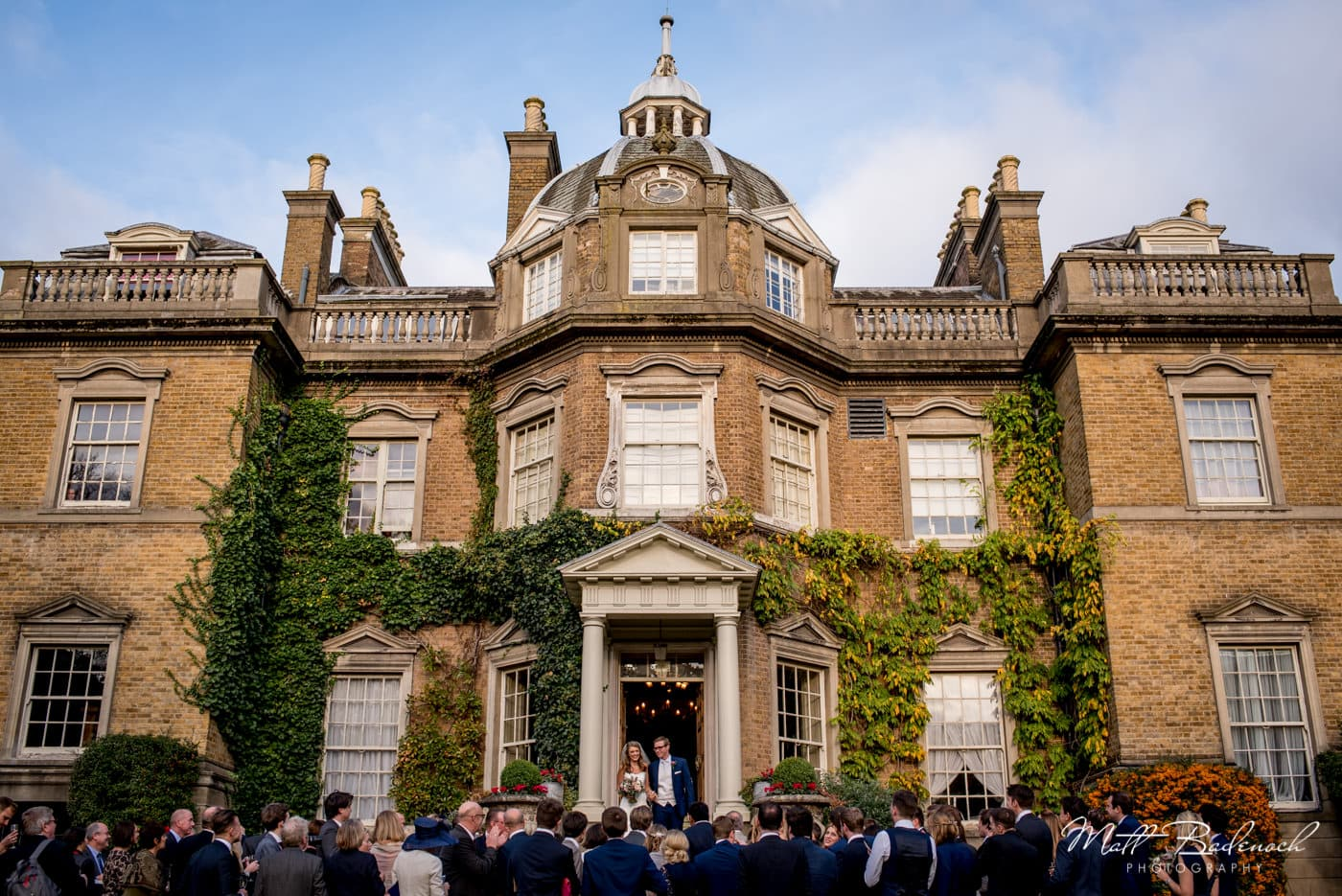 Guests outside for couple's Hampton Court House Wedding in winter
