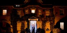 creative flash portrait of bride and groom outside Hampton Court house at night