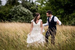Featured on Your Perfect Wedding Photographer - photo of bride and groom laughing in a field