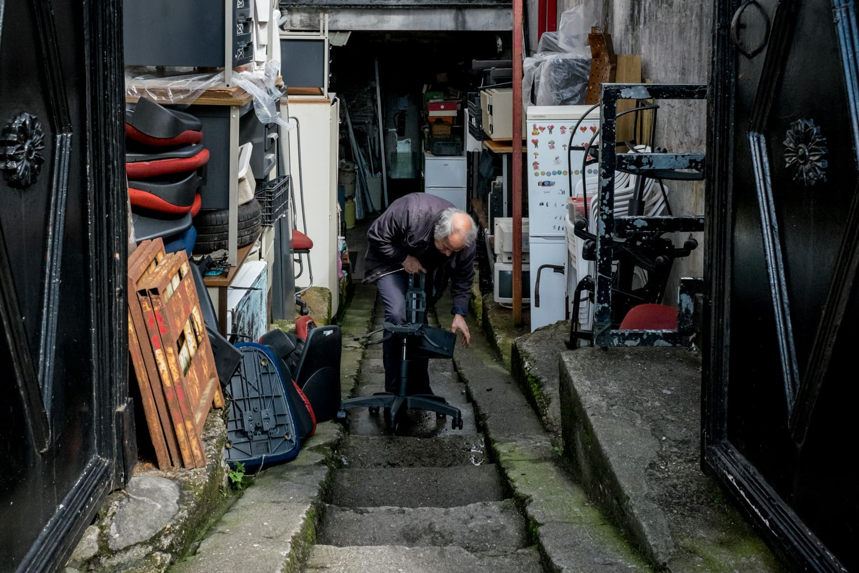 photos of porto of a man fixing a chair in his workshop