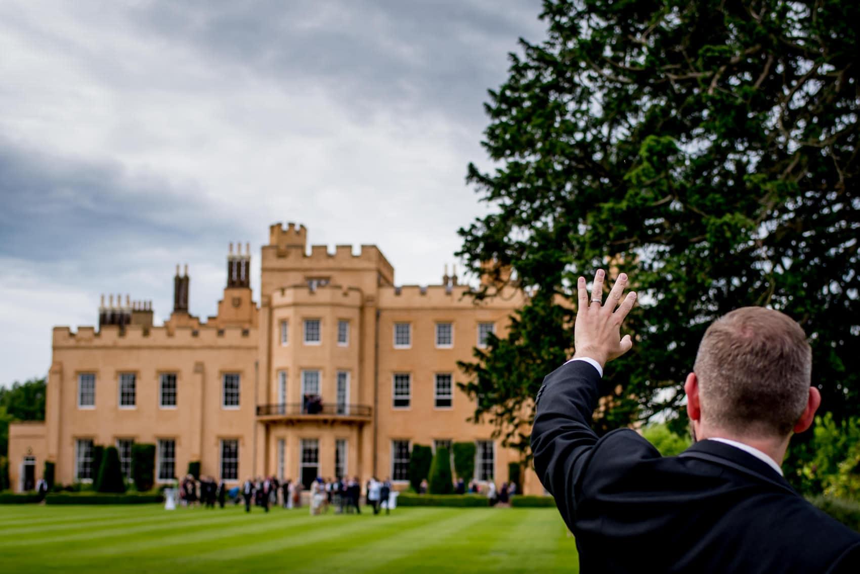 Groom waving at his wedding guests at Ditton Park