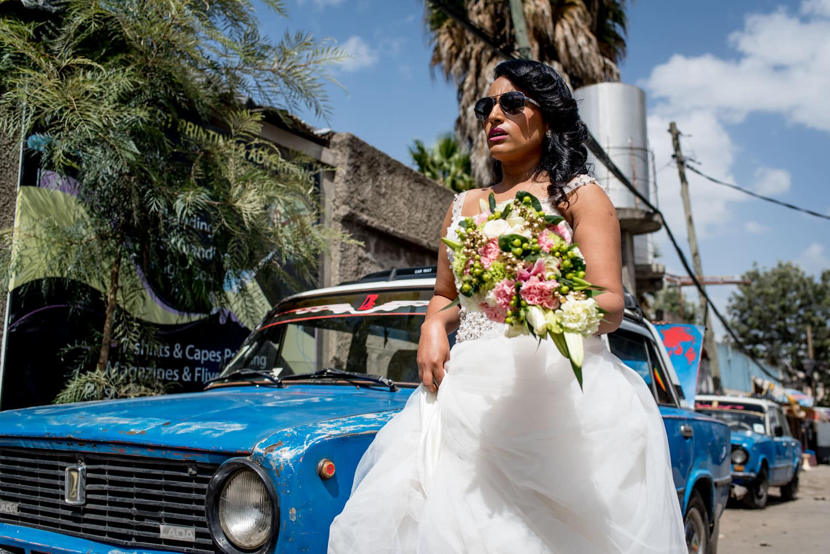 Wedding bride in Addis Ababa in front of a blue Landa taxi