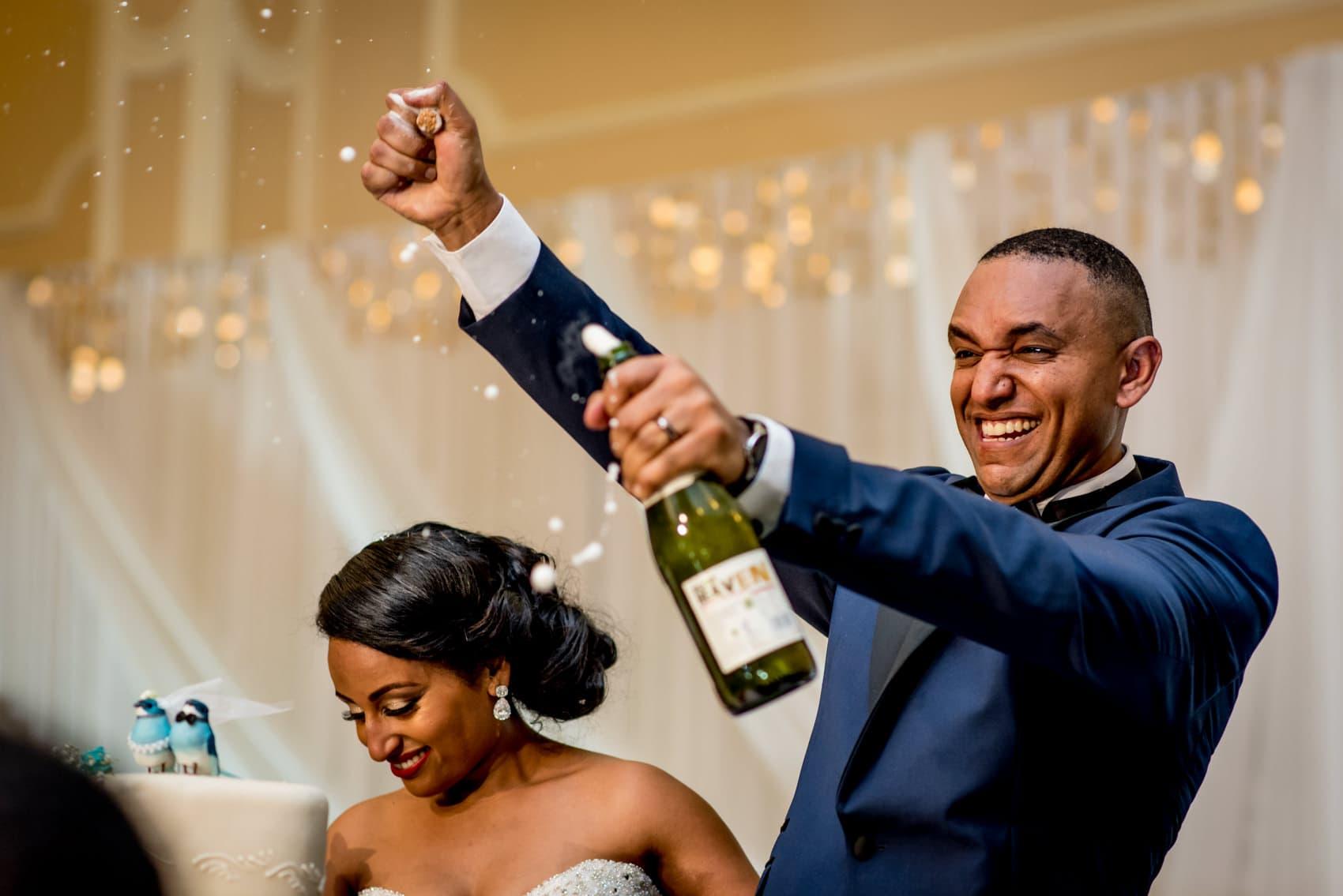 groom pulling cork off a bottle of wine