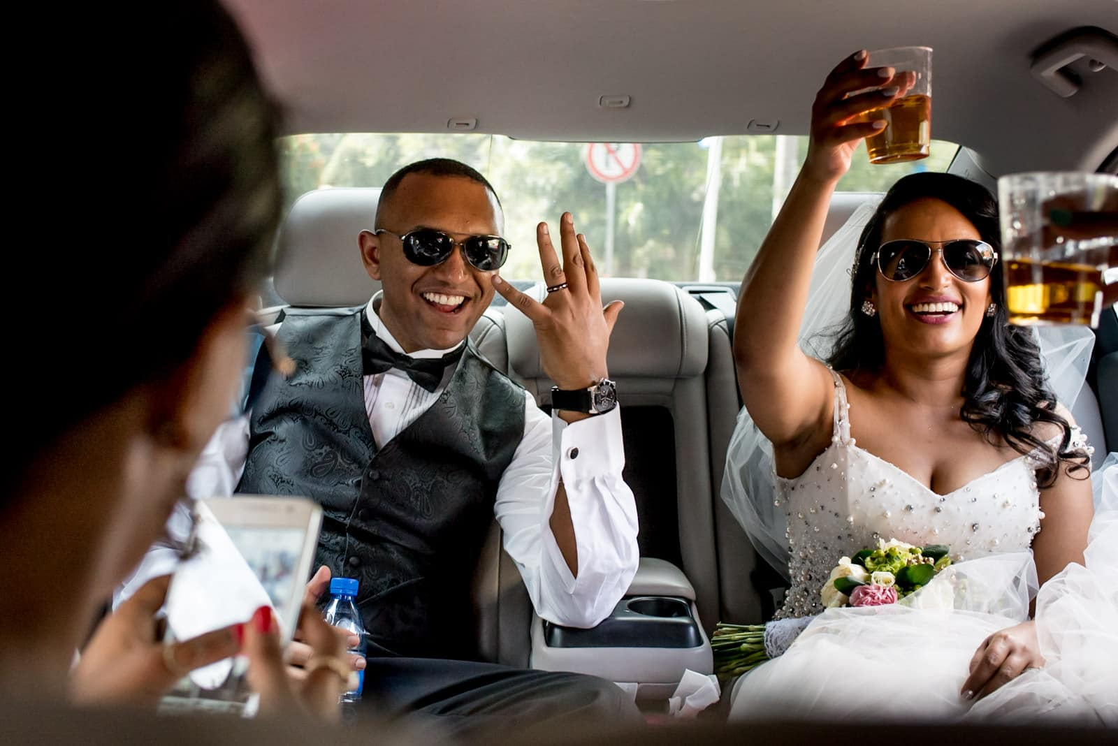 Ethiopian bride and groom drinking Johnny Walker Black whisky in a limo in Addis