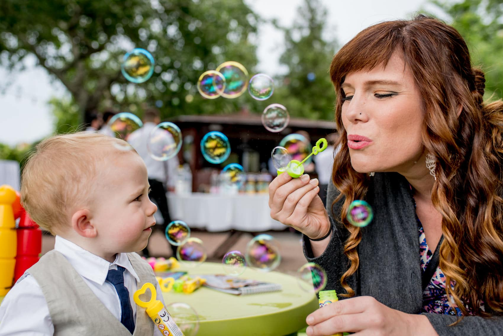 girls plays with bubbles with a young boy