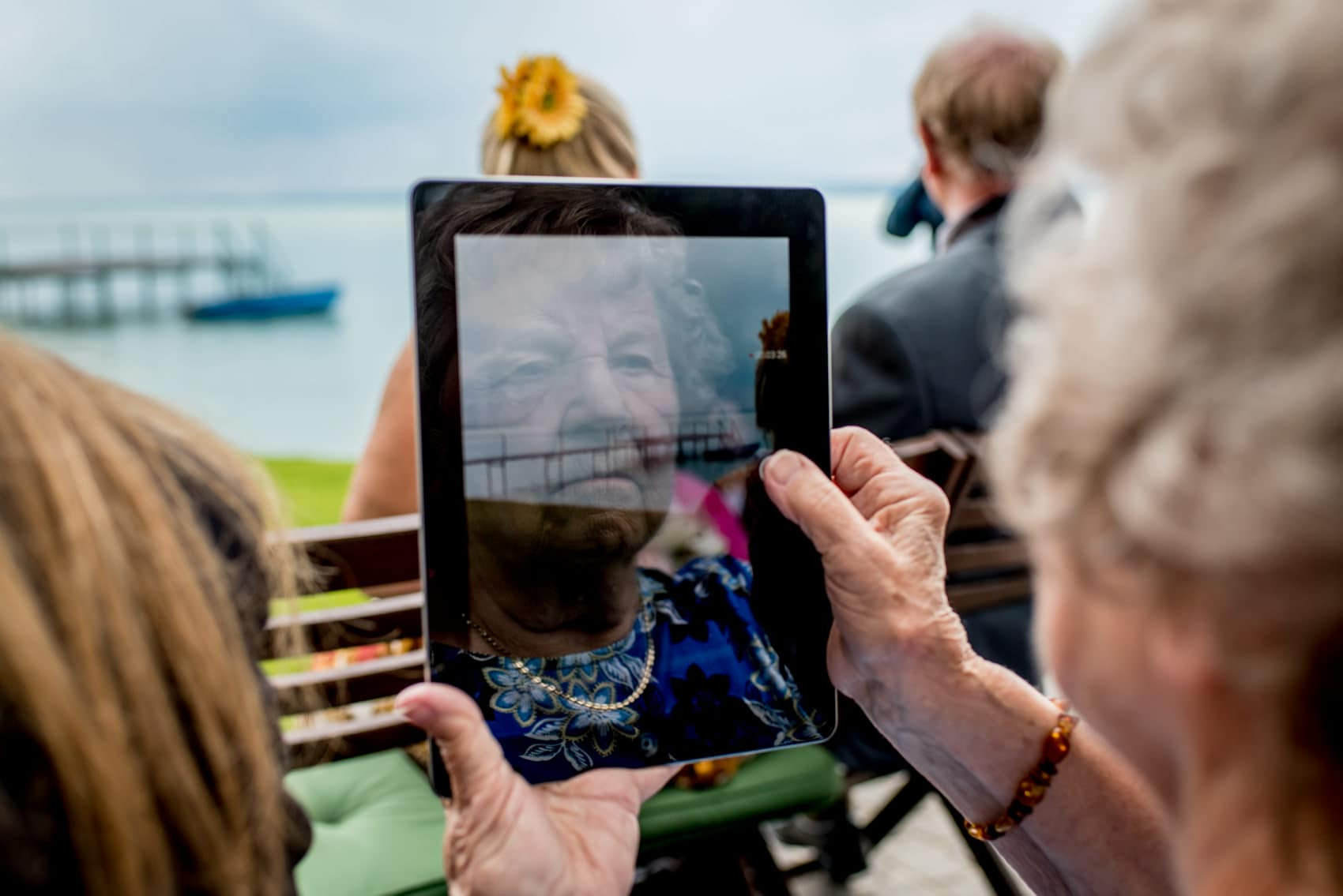 grandmother at lake balaton with her reflection in an ipad