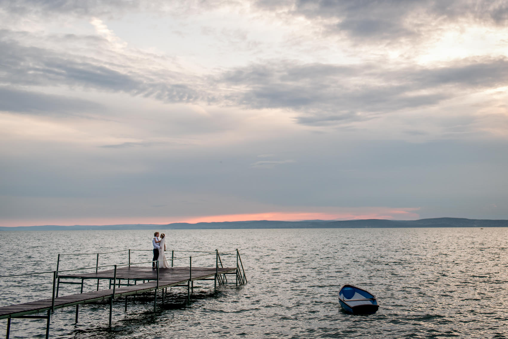 bride and groom on the pier of a lake in Hungary