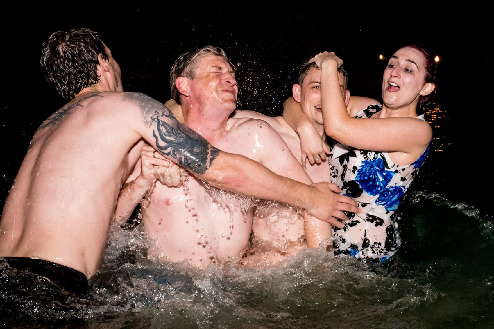 night time fun with guests playing in the lake at a wedding