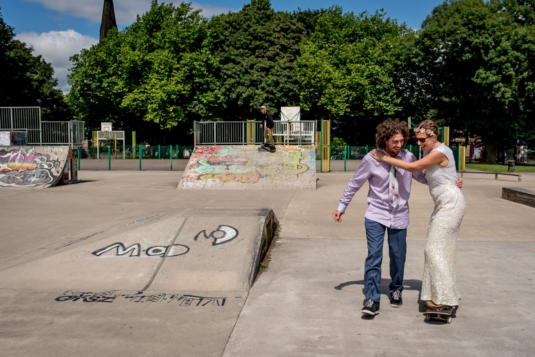 bride and groom skateboarding at their wedding at the skate park