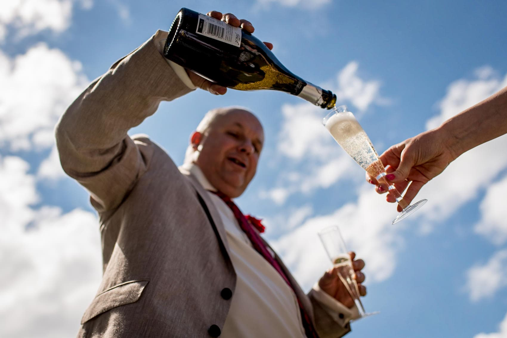 pouring champagne at the wedding reception with blue skies