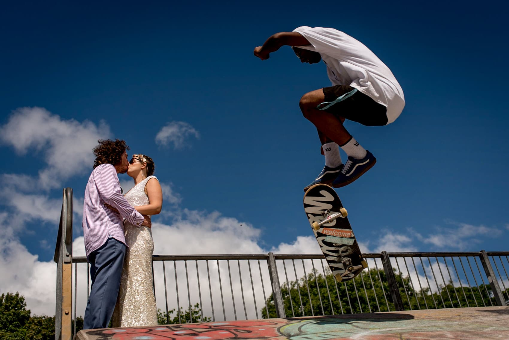 alternative bride and groom skateboarding portrait