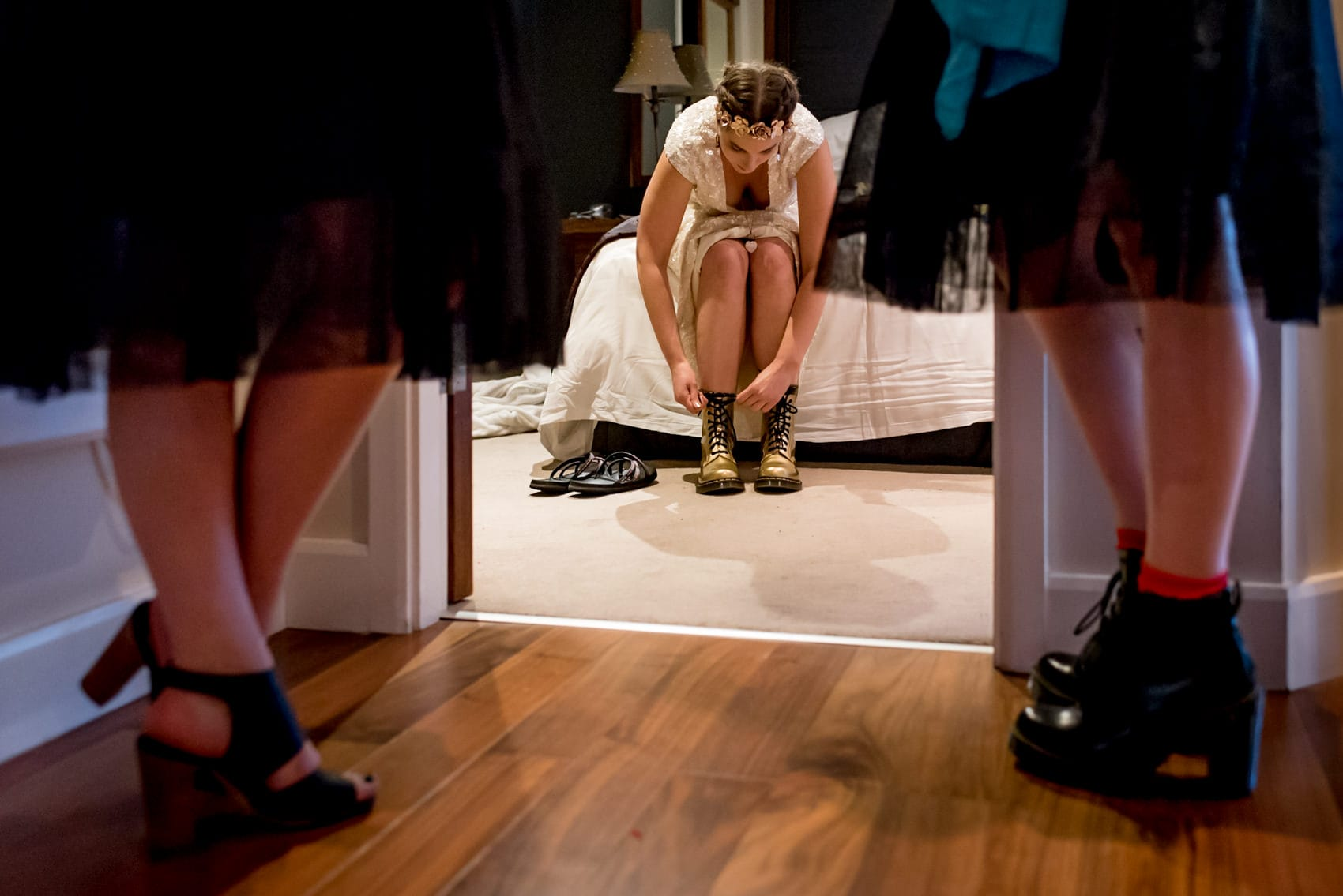 bride putting on her gold doc martins for her alternative wedding in Leeds