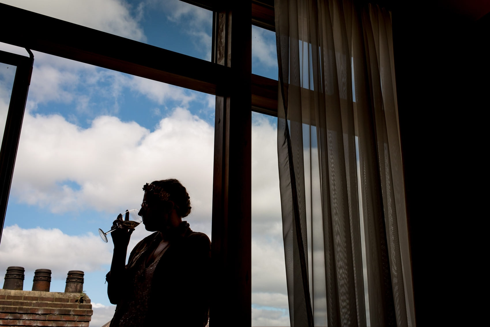 silhouette of a bride with a glass of wine while she gets ready for her wedding