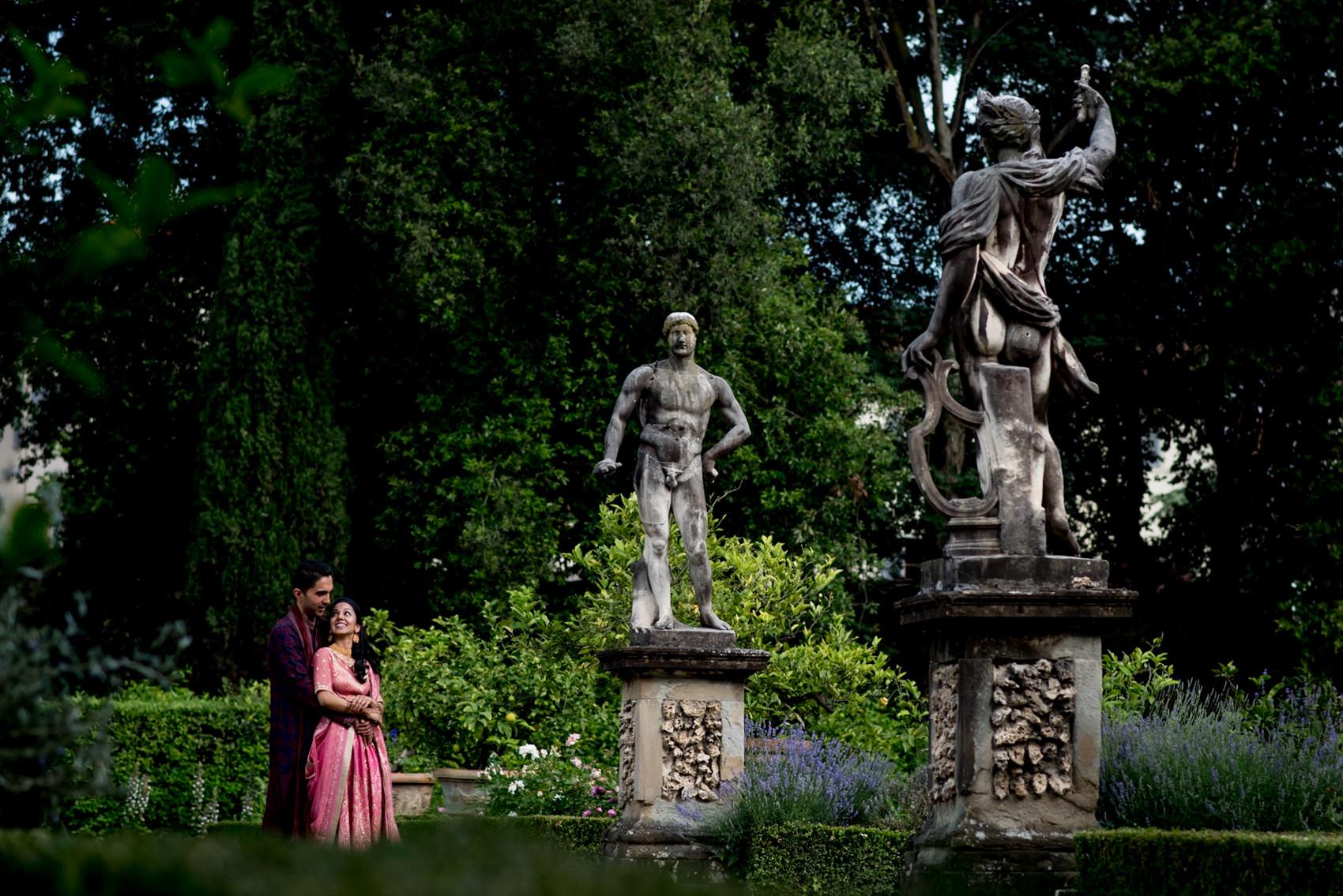 Indian posing next to statures at Giardino Corsini al Prato in Florence