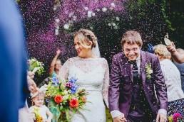 Purple glitter confetti thrown at wedding couple