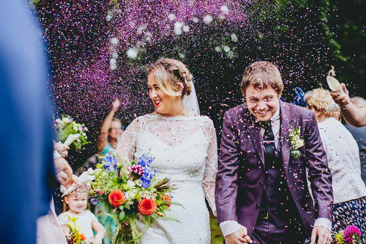 Purple glitter confetti thrown at wedding couple