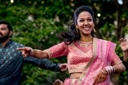 indian bride in pink dress dancing at her Florence wedding in Italy