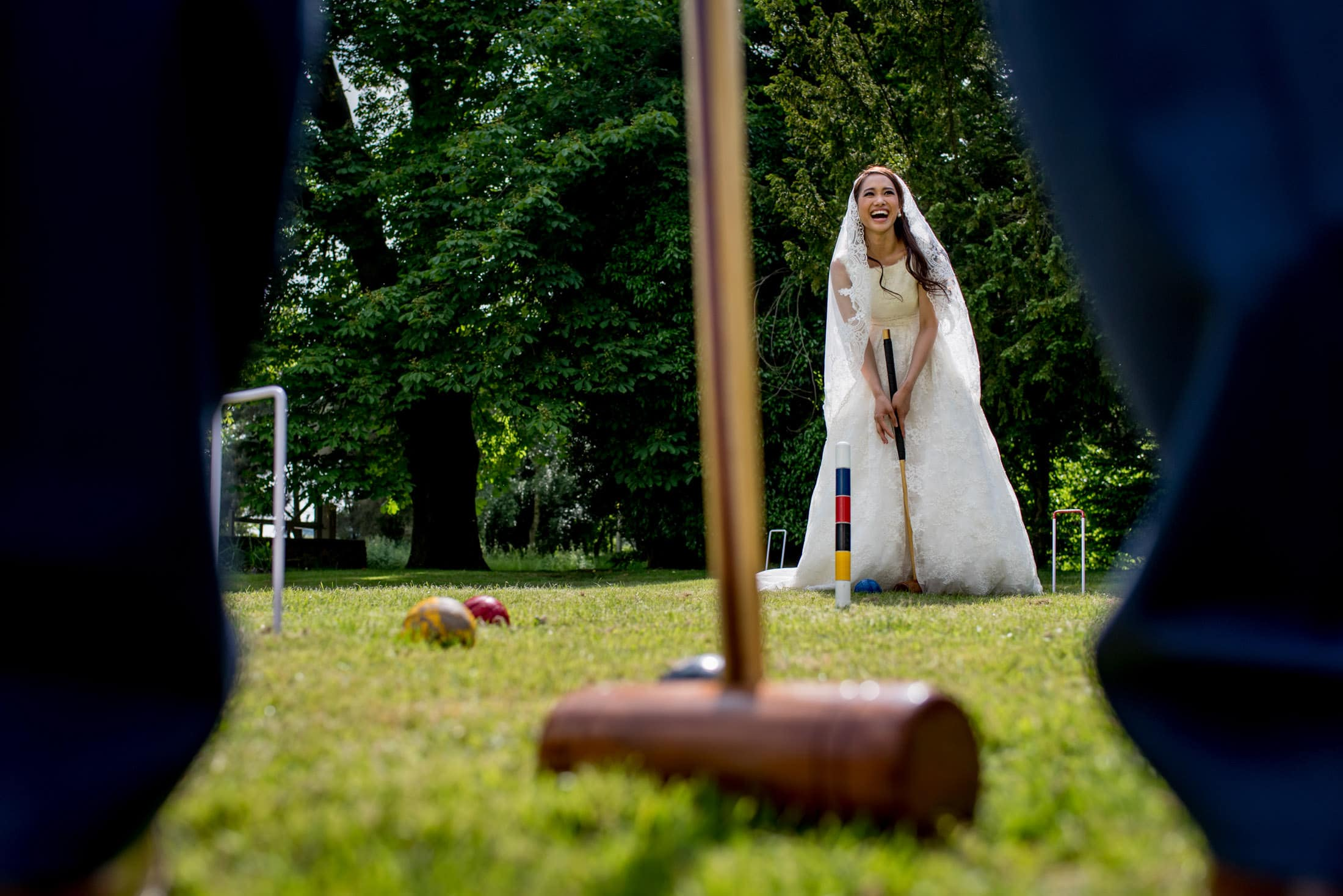 Photo of bride in her wedding dress playing croquet