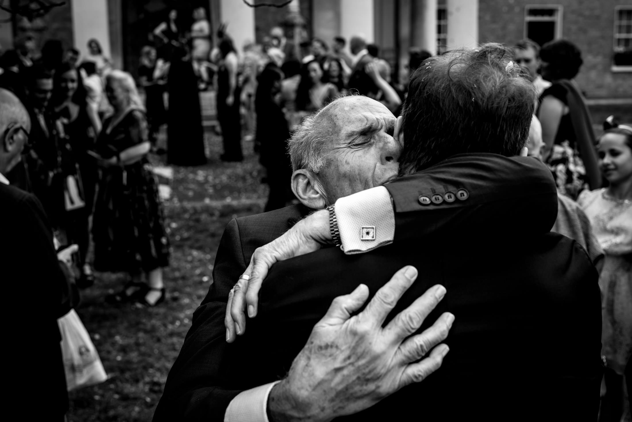 Black and white photo of dad embracing his son at his wedding taken by London wedding photographer Matt Badenoch