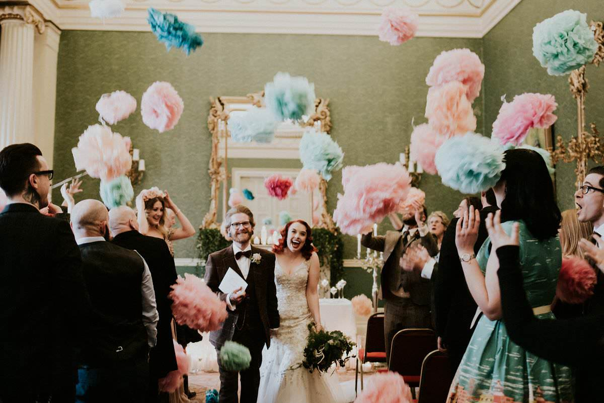 Giant pompom confetti being thrown at wedding couple
