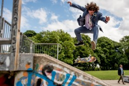 groom in blue suite jumping on a skate board