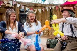 balloon twister teaching girls how to make balloon animals at a wedding
