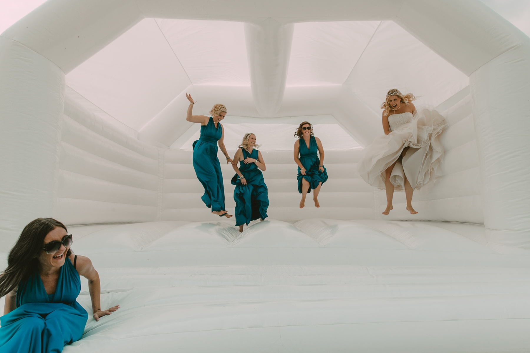bride and bridesmaids bouncing on a white bouncy castle at a wedding
