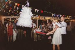 bride hitting a wedding cake pinata at her wedding