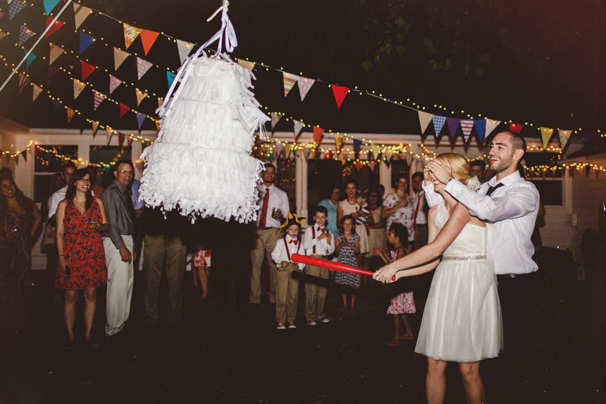 bride hitting a wedding cake pinata at her wedding