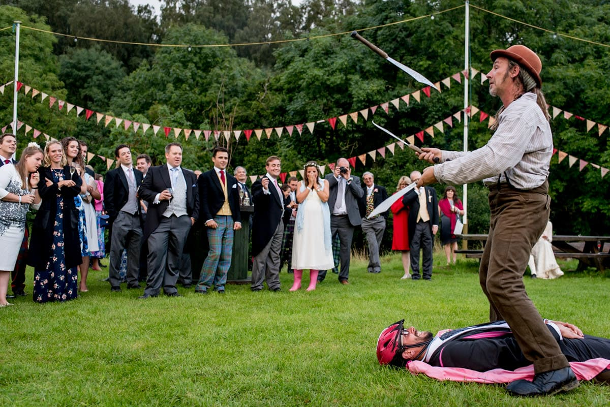 a circus entertainer juggling knives at a festival wedding
