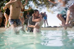 guests bombing wedding couple in pool like human confetti