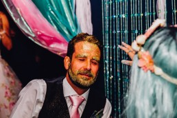groom having his face covered in gold glitter at his wedding