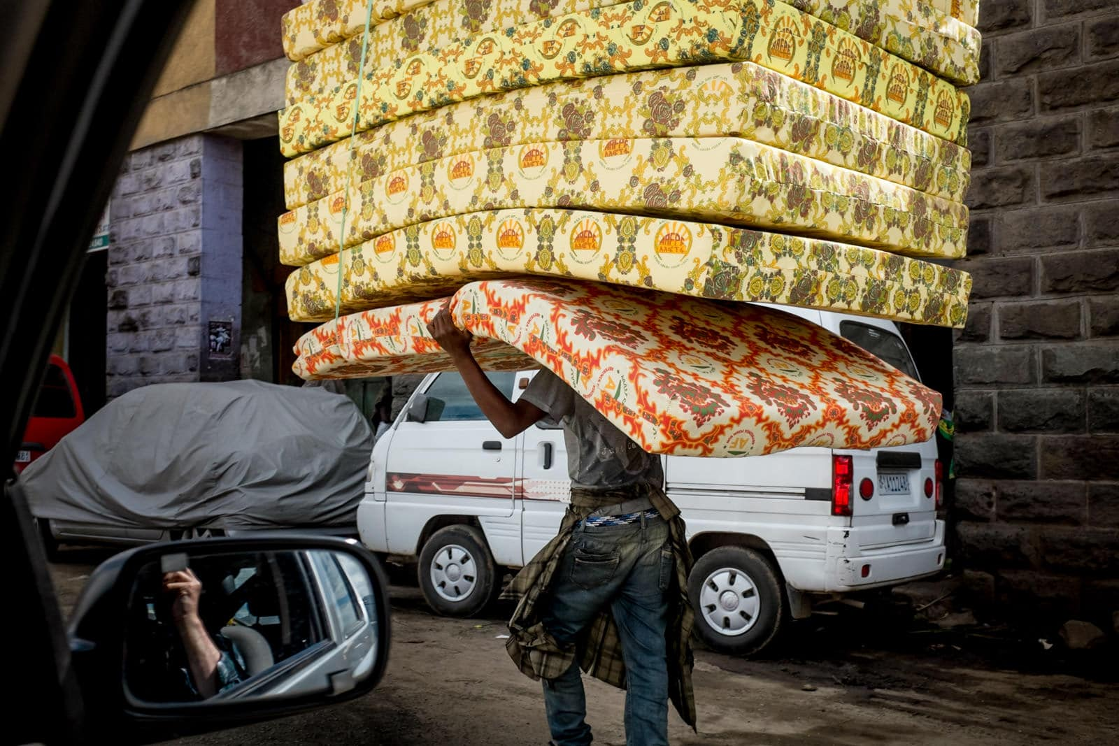Man carrying stacked mattresses in Addis Ababa, Ethiopia, Africa