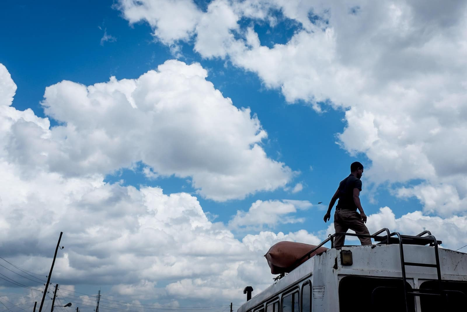 Addis Ababa street photography in Ethiopia with man on top of bus in front of clouds