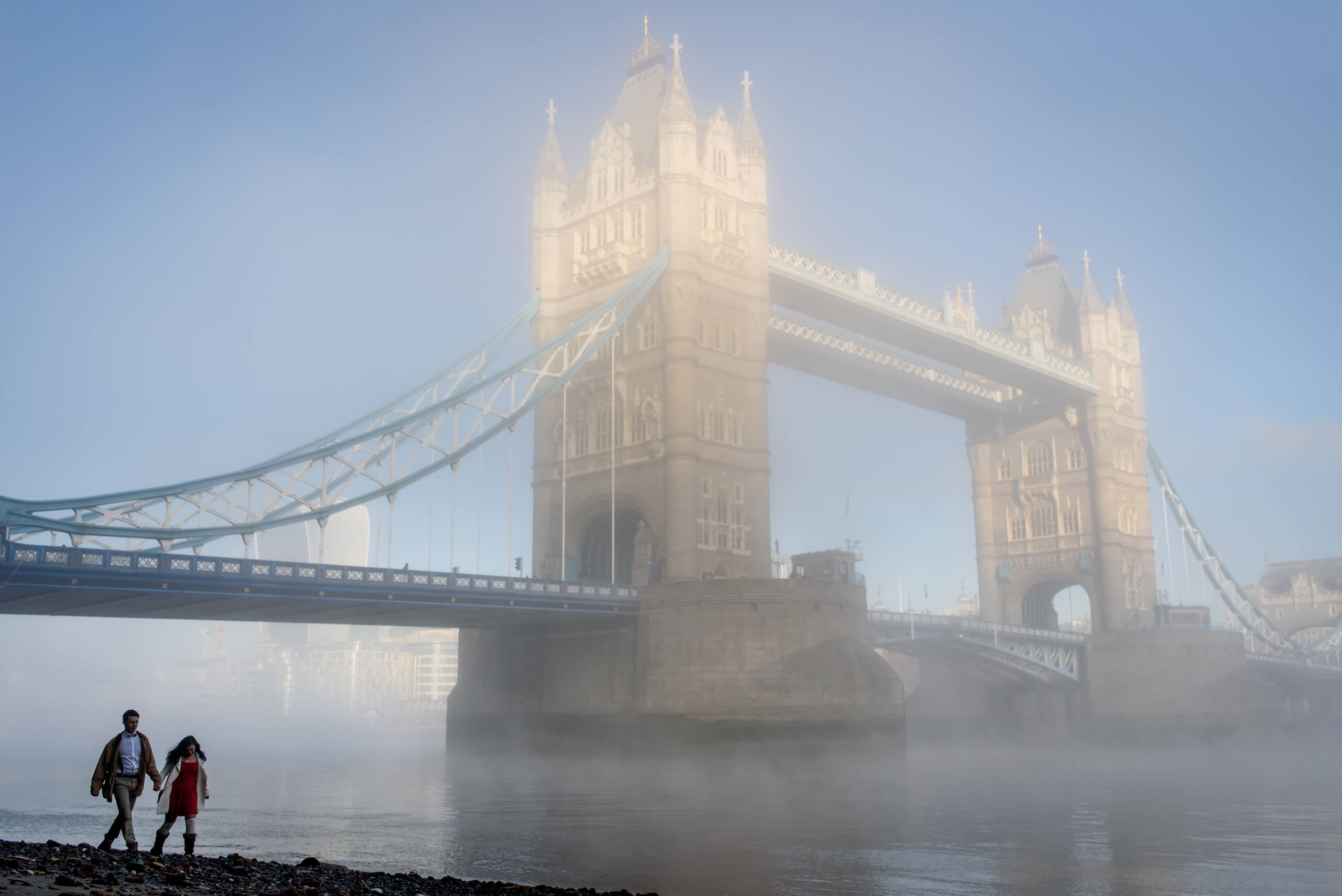 A couple walking along the bank of the Thames next to Tower bridge in the mist for their central London engagement photography shoot.