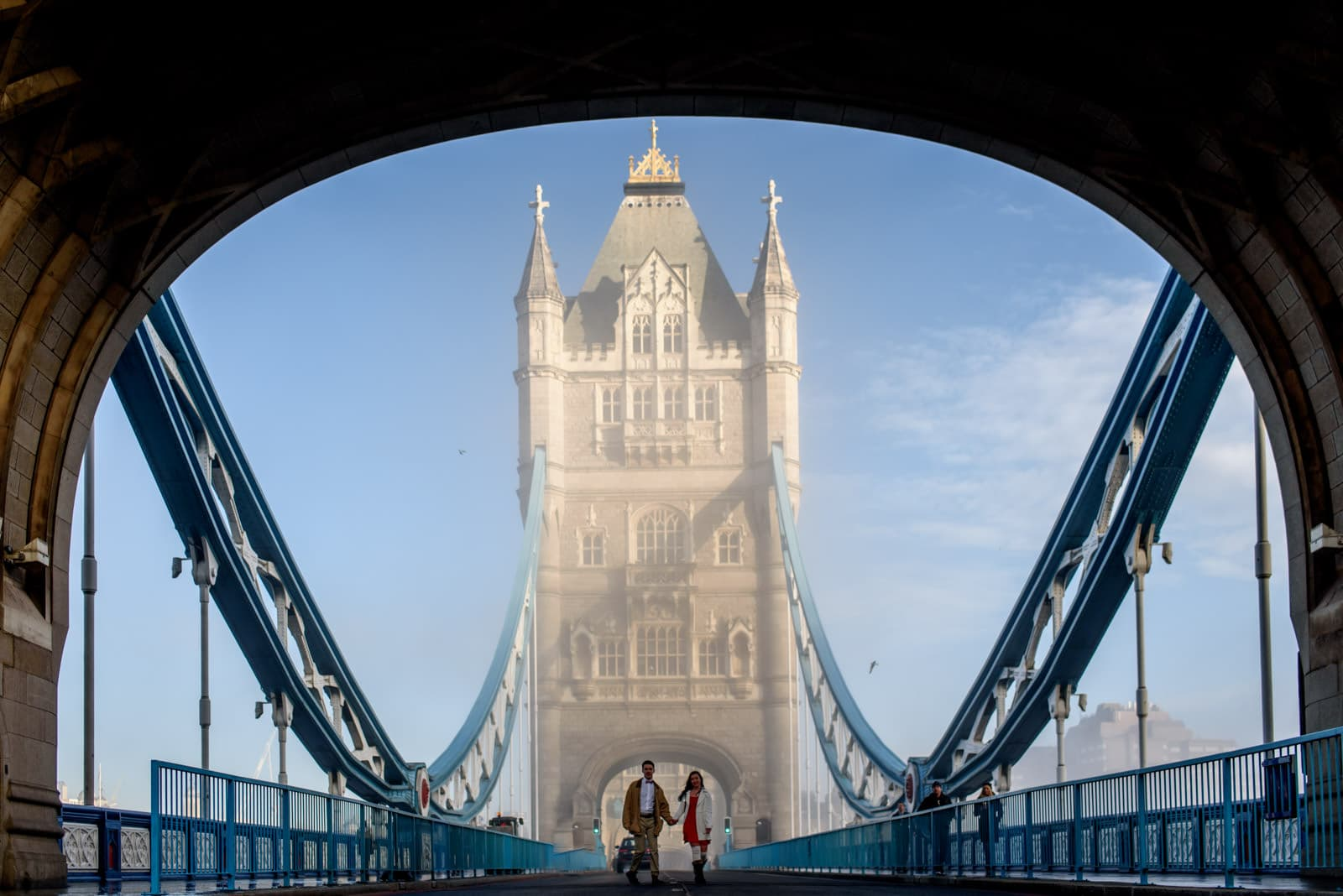 Engaged couple walking across Tower Bridge in the winter.