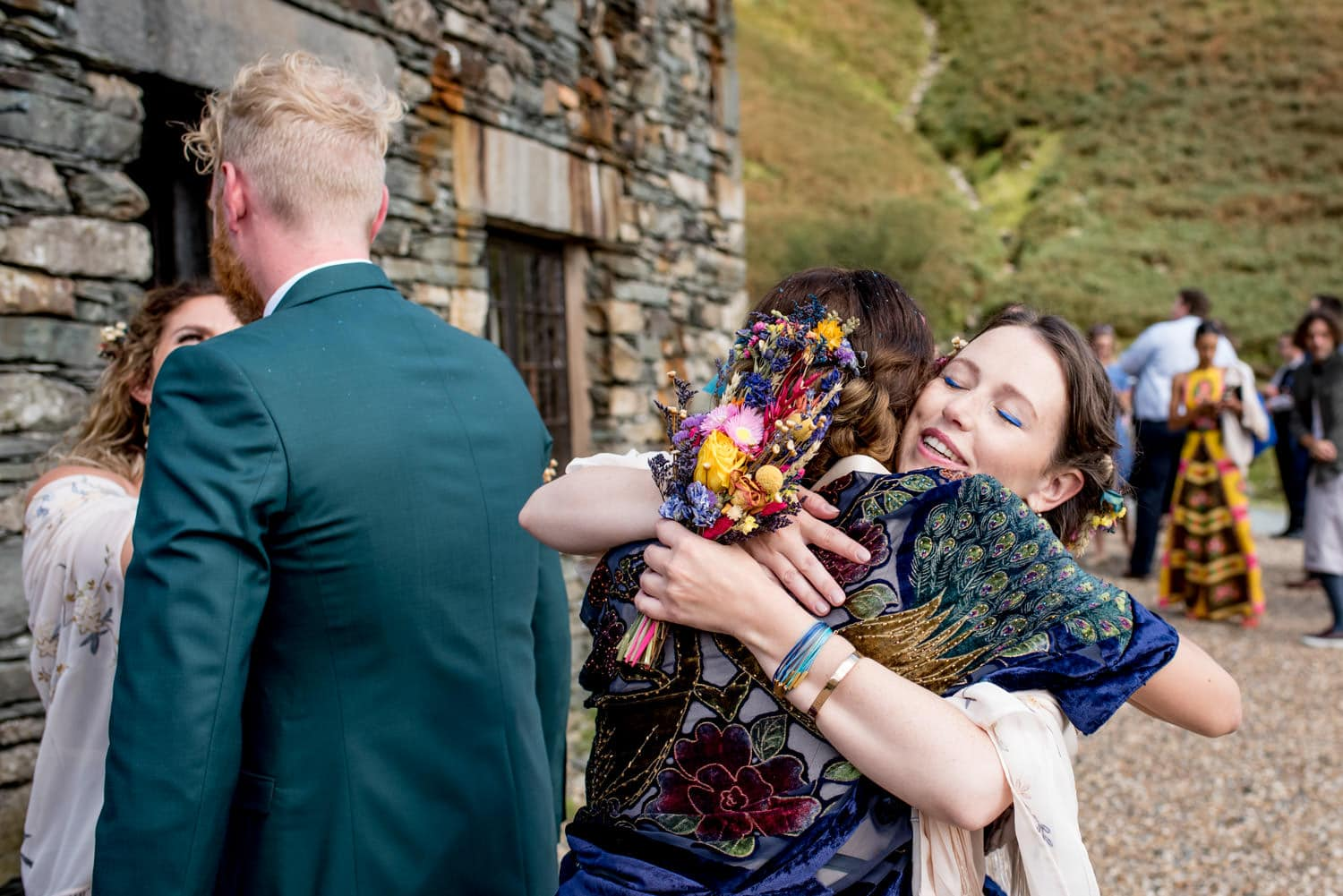 Bridesmaid hugging bride at their wedding in the Lake District