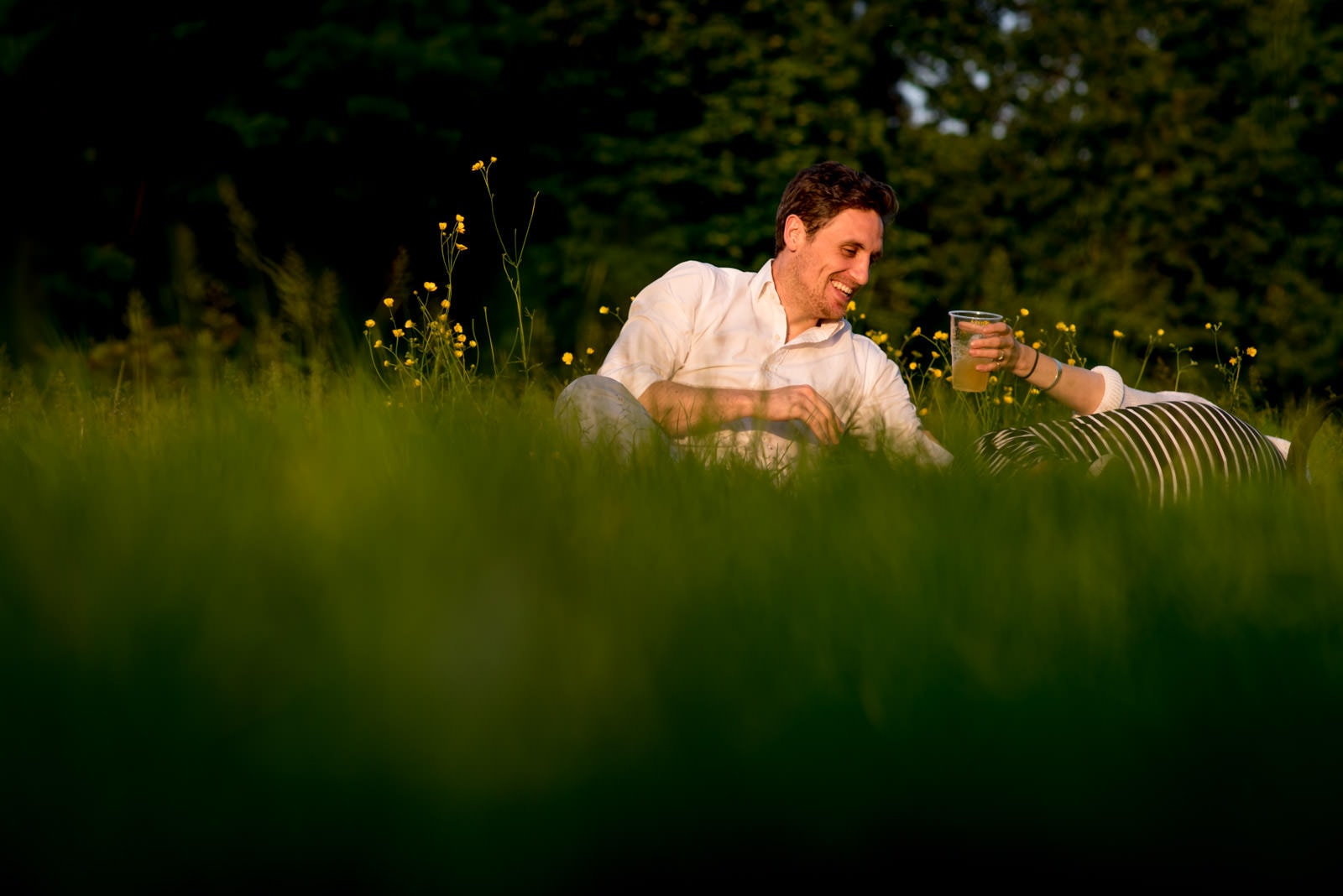 Couple playing in the grass during their engagement pictures in regents park