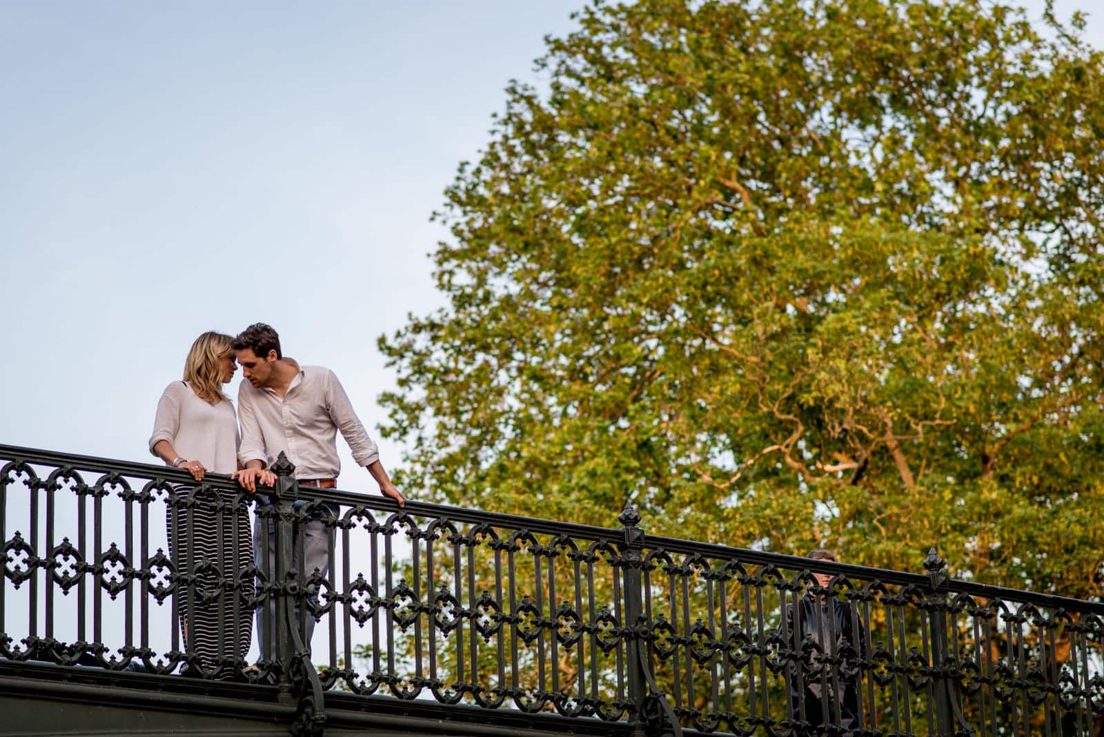 Couple on bridge over canal and next to a tree in north London for their engagement pictiures