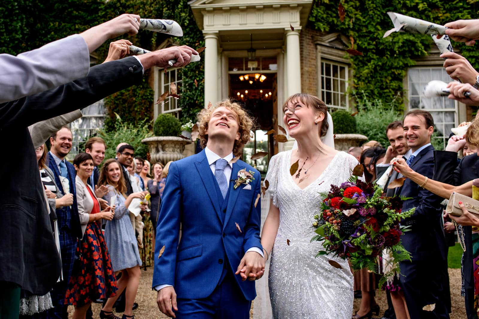 Confetti photo with bride and groom in blue suit at Hampton Court