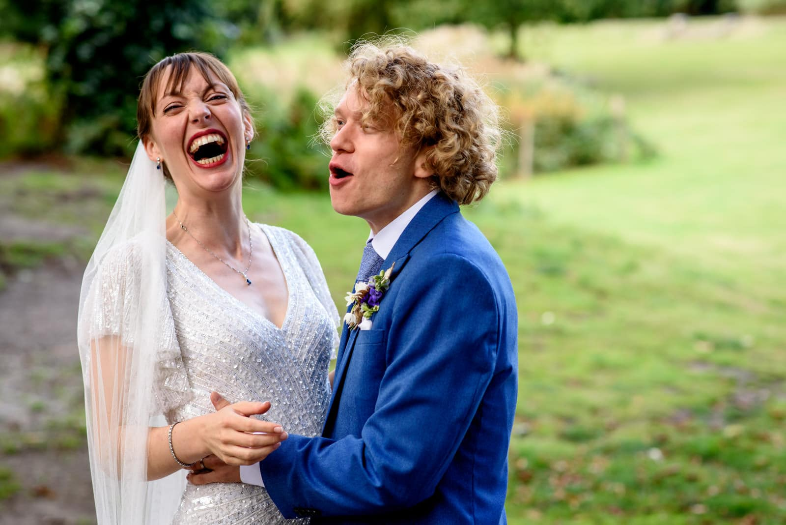 Bride and groom in blue suit laughing during portraits