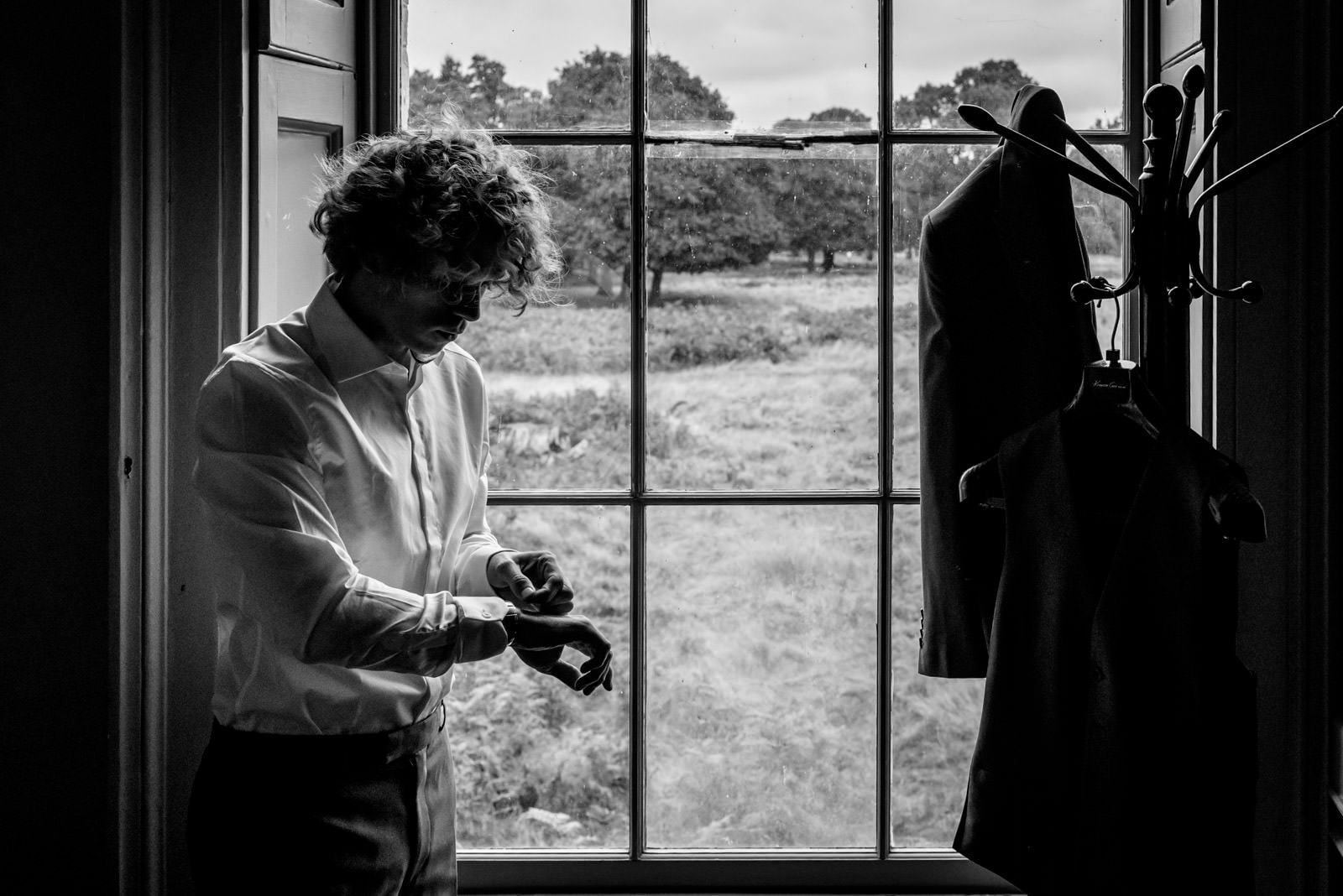 Groom getting ready at hampton court house in front of the window over looking Bushy park