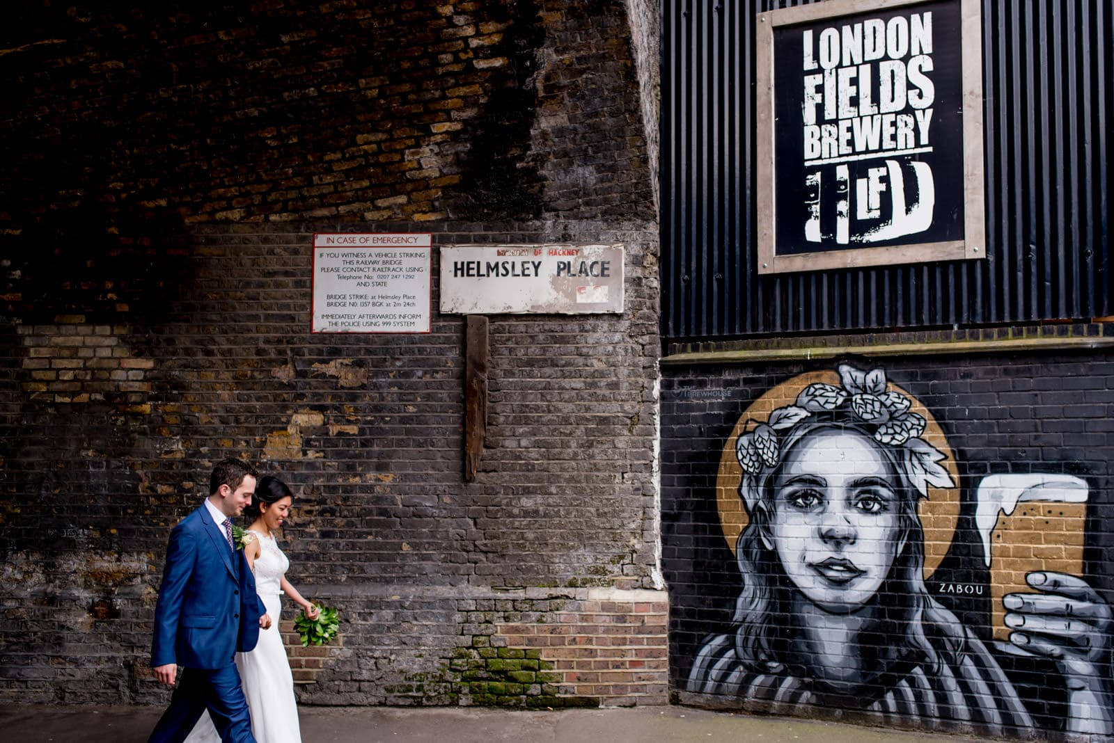 bride and groom walking past London Fields brewery sign for their wedding