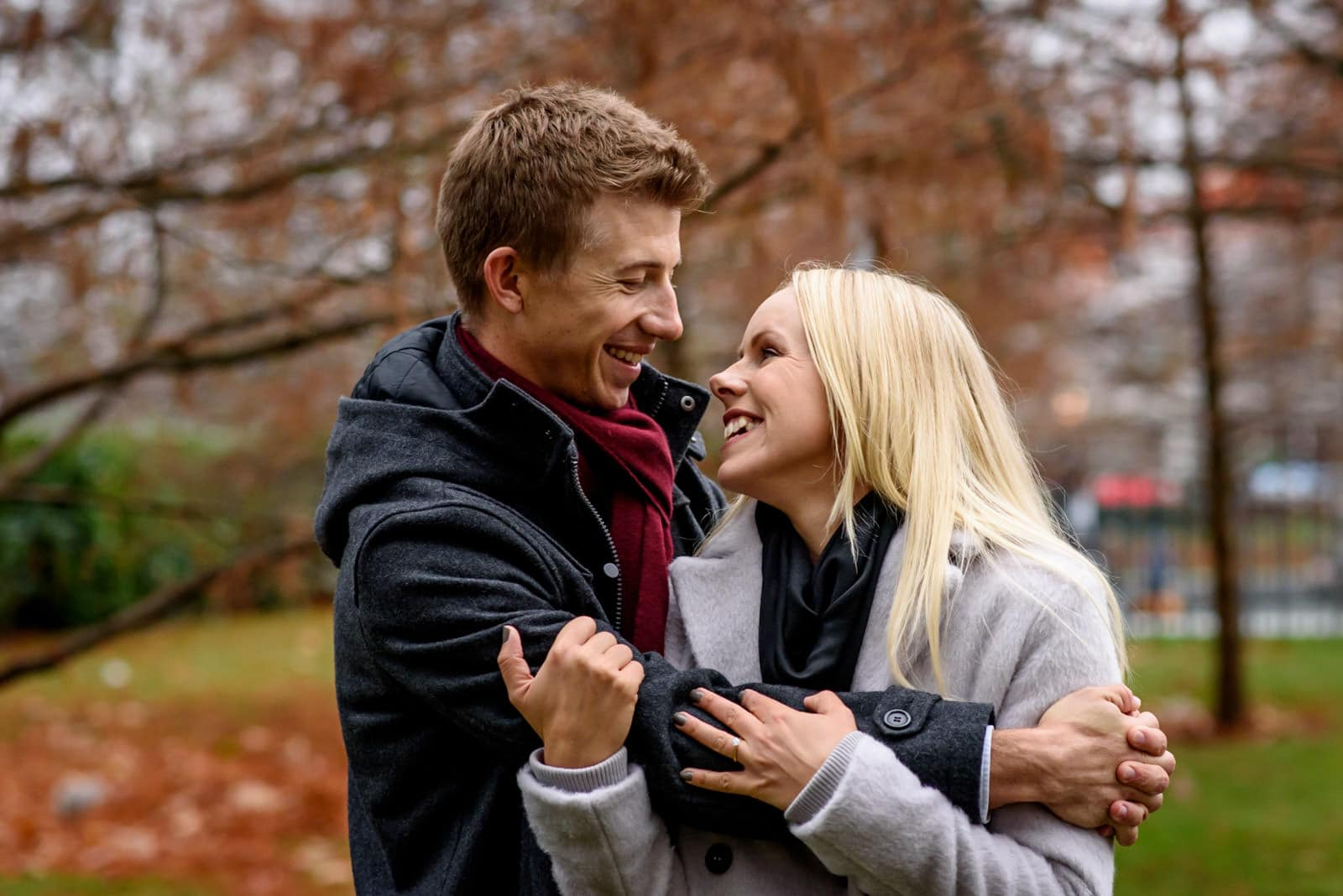 Engaged couple in London park with brown Autumn leaves.