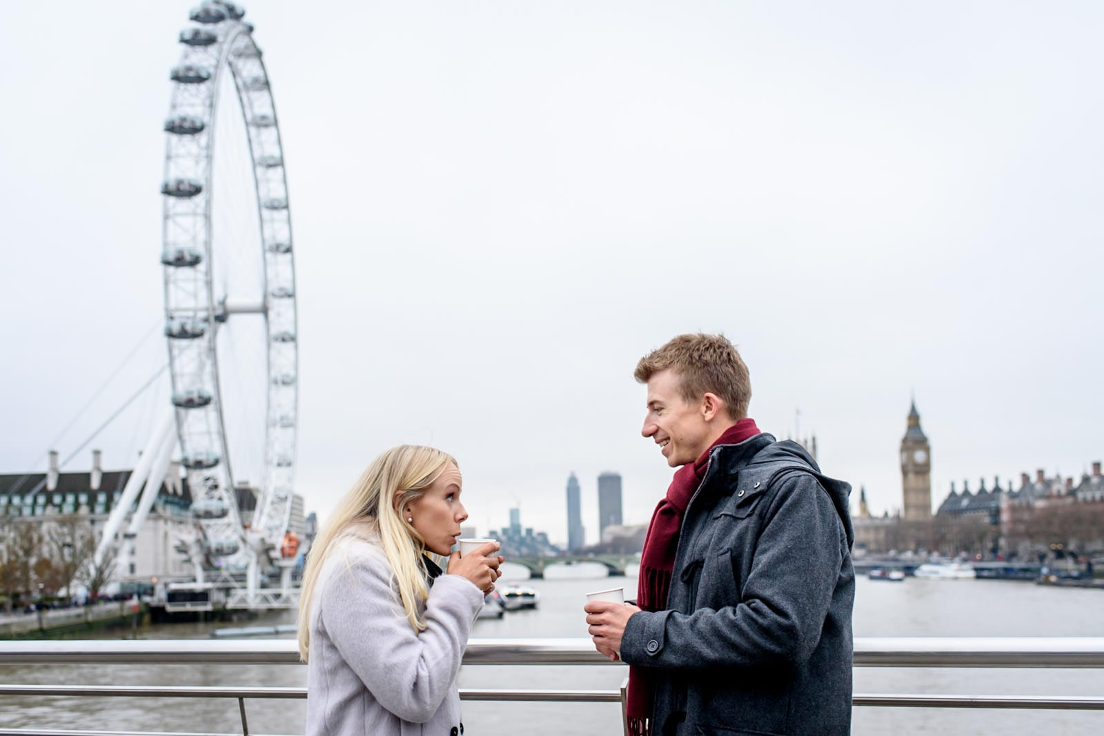 Engaged couple drinking mulled wine on bridge over thames in front of the London Eye