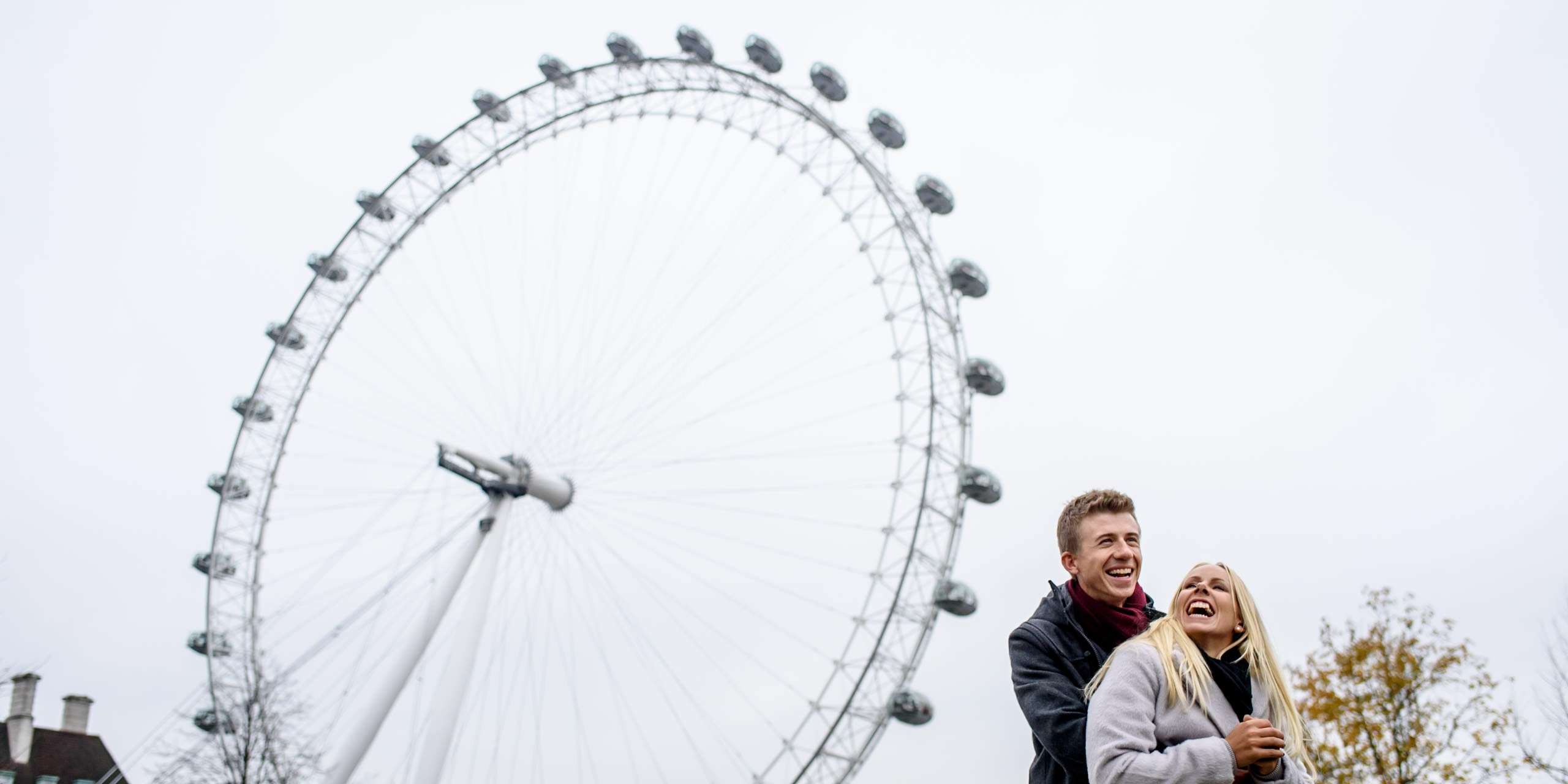 Laughing couple in front of the London Eye for their winter engagement photography session