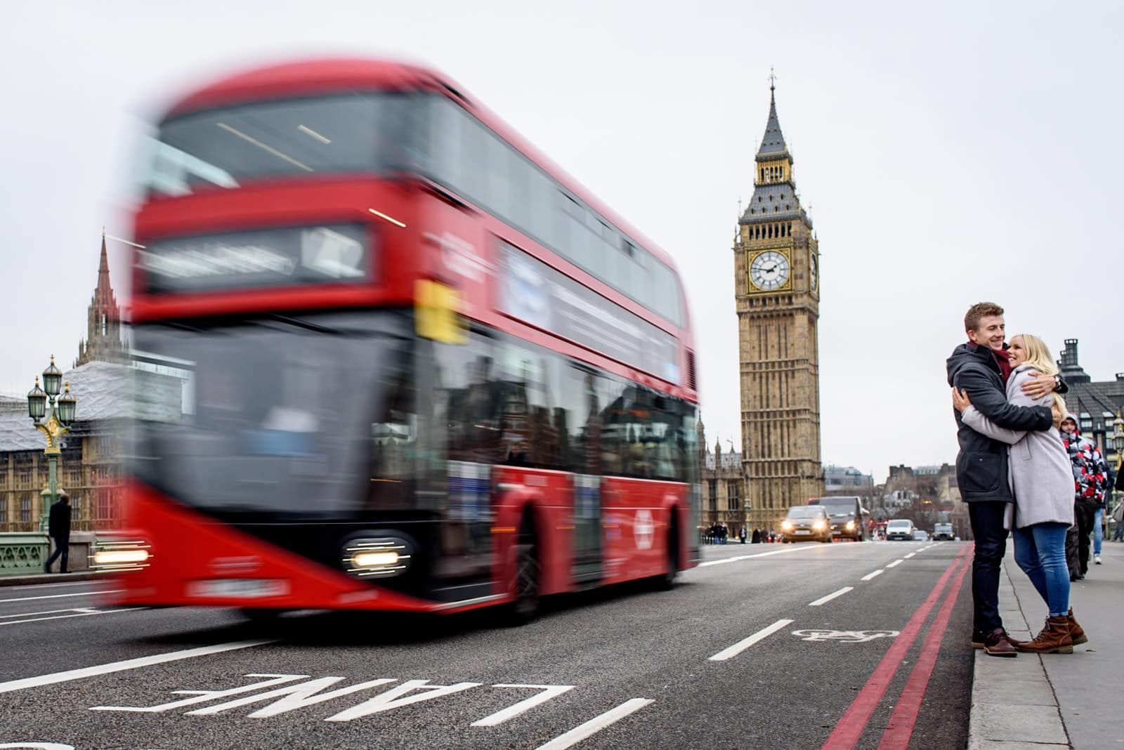 Couple hugging on Westminster Bridge with Big Ben and a Red London Bus