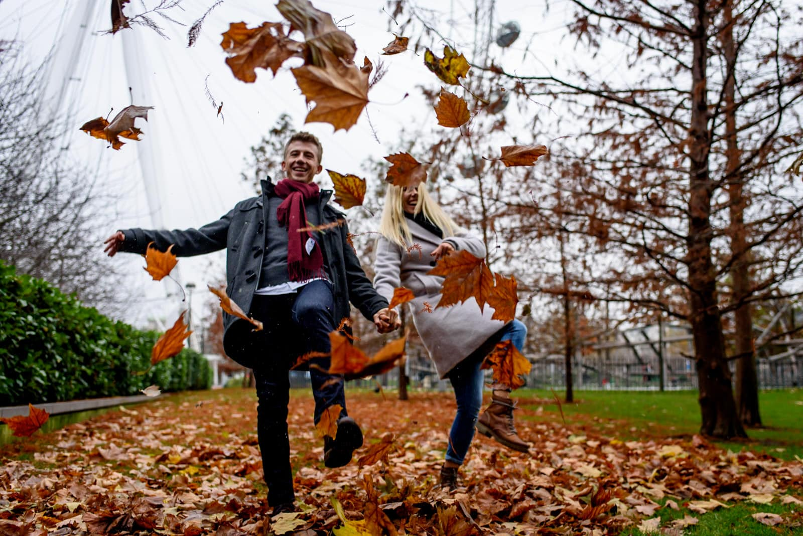 Young couple playing in brown autumn leaves in front of the London Eye