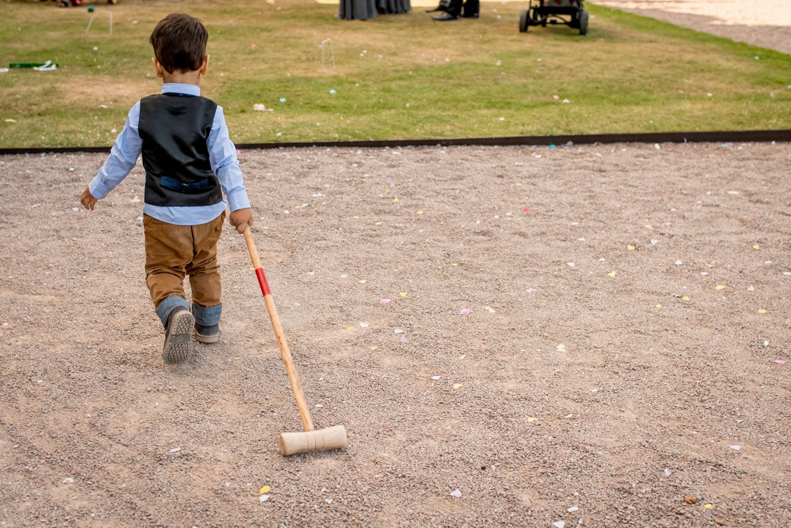 Kid walking with a croquet mallet during garden games at Moor Park Golf Club